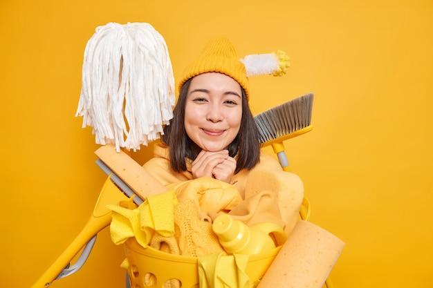 Nettoyant femme au foyer souriant sur jaune