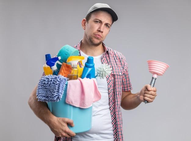 Nettoyant jeune homme confiant portant une casquette tenant un seau d'outils de nettoyage avec piston isolé sur fond blanc