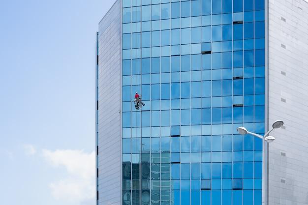 Nettoyant pour vitres travaillant sur une façade en verre suspendue