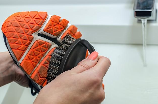 Nettoyer les baskets sales après l'entraînement. lavez les baskets sales. lavez vos baskets. nettoyer sa chaussure de trail running.