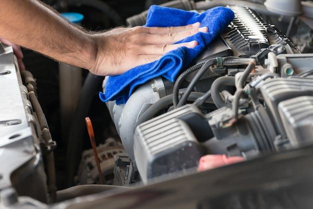 Nettoyer le moteur de la voiture avec un chiffon microfibre bleu