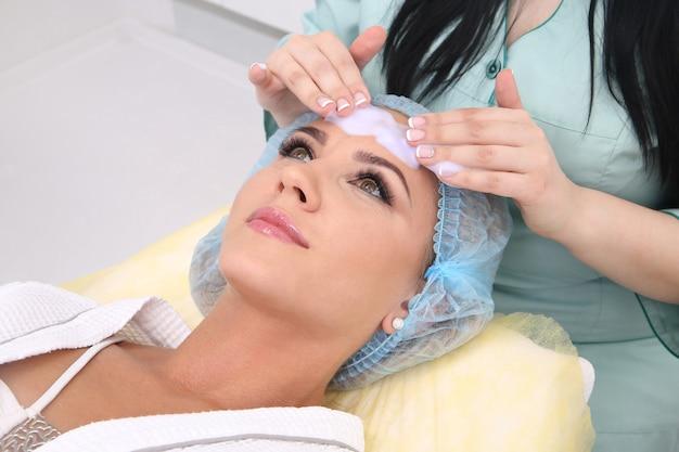 Nettoyer la peau avec de la mousse, une belle femme dans la beauté du salon de beauté