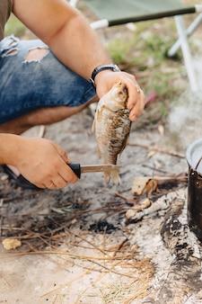 Nettoyer et trancher le poisson pour le bouillon de poisson dans la nature près du feu