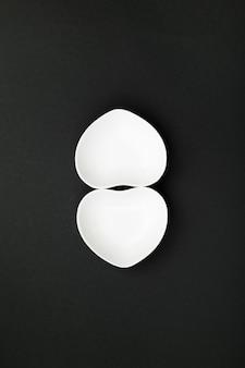 Nettoyer la vaisselle blanche en forme de coeur sur fond noir. vue de dessus