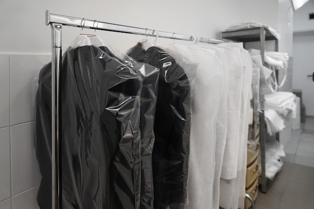 Nettoyer les vêtements emballés suspendus dans l'atelier du nettoyeur à sec