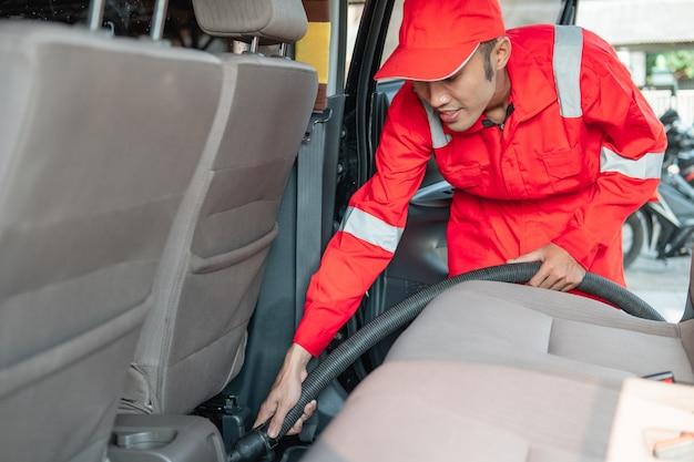 Nettoyeur de voiture mâle portant l'uniforme rouge nettoie le plancher de la voiture avec un aspirateur en voiture