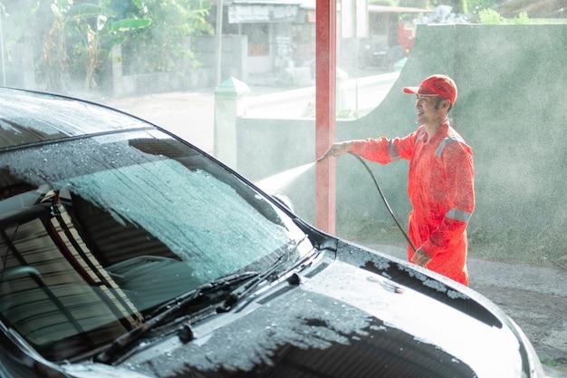 Nettoyeur de voiture mâle portant un uniforme rouge pulvérise de l'eau sur la voiture tout en lavant la voiture