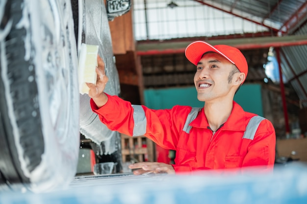 Nettoyeur de voiture mâle porte uniforme rouge et chapeau souriant tout en lavant la voiture avec une éponge mousseuse dans un salon de voiture