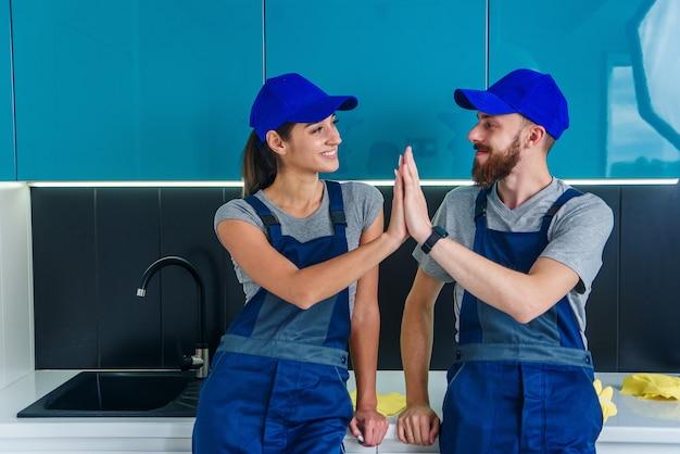 Des nettoyeurs satisfaits en uniformes bleus se donnant un high five et continuant à nettoyer le sol dans la cuisine.