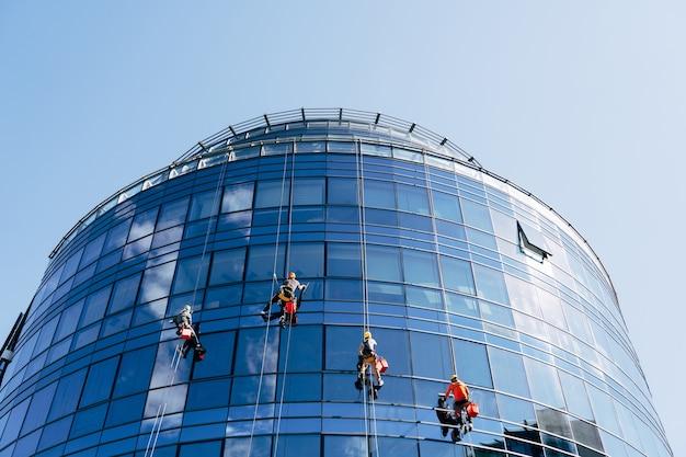 Les nettoyeurs de vitres lavent les fenêtres en miroir bleu à l'extérieur du bâtiment