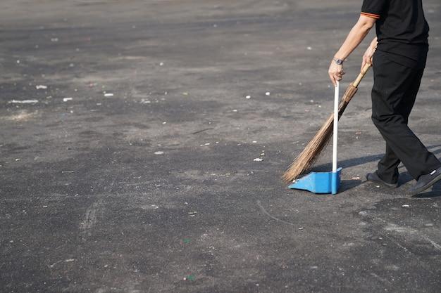 Nettoyez les déchets de balayage dans la grande zone extérieure d'asphalte à midi.