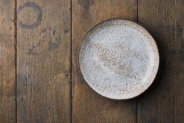 Nettoyez la plaque en céramique vide sur le fond en bois brun foncé horizontal au-dessus de l'espace de copie