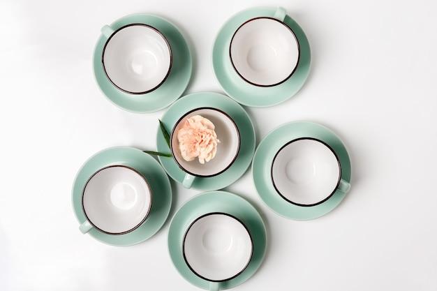 Nettoyez la vaisselle, le café ou le thé. beaucoup d'élégantes tasses et soucoupes en porcelaine avec une fleur à l'intérieur, une touche haute, une vue de dessus et une pose à plat.