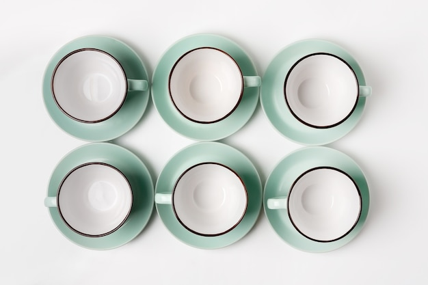 Nettoyez la vaisselle, le café ou le thé. beaucoup d'élégantes tasses et soucoupes en porcelaine, high key, vue de dessus et pose à plat.