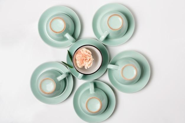 Nettoyez la vaisselle, le café ou le thé. composition d'élégantes tasses et soucoupes en porcelaine avec fleur à l'intérieur, high key, vue de dessus et pose à plat.