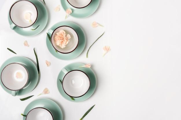 Nettoyez la vaisselle, le café ou le thé. composition d'élégantes tasses et soucoupes en porcelaine avec pétales de fleurs, high key, vue de dessus et pose à plat.
