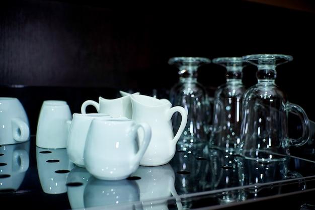 Nettoyez la vaisselle sur une étagère en verre avec un reflet sombre.