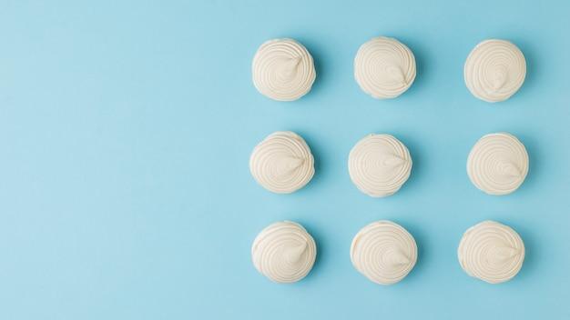 Neuf meringues fraîches sur un bleu. délicieuse douceur des œufs et du sucre.