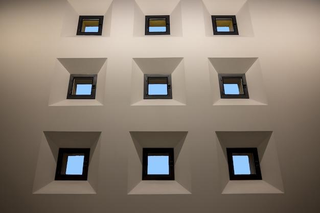 Neuf petites fenêtres isolées sur mur blanc