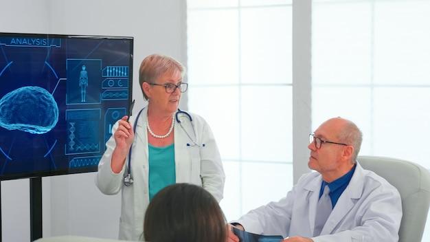 Neurologue lisant les ondes cérébrales sur le moniteur pendant que le médecin porte un casque avec des capteurs. le moniteur montre une étude cérébrale moderne tandis qu'une équipe de scientifiques ajuste l'appareil travaillant dans la salle de conférence de l'hôpital