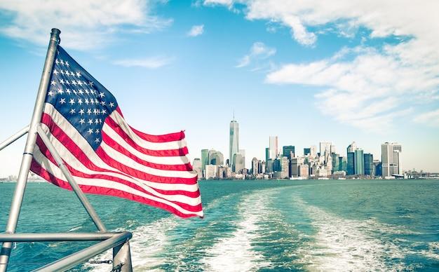 New york et manhattan depuis la rivière hudson avec drapeau américain
