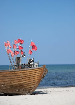 Nez de bateau de pêche sur une plage de sable avec plusieurs petits drapeaux rouges sur les mâts de drapeau