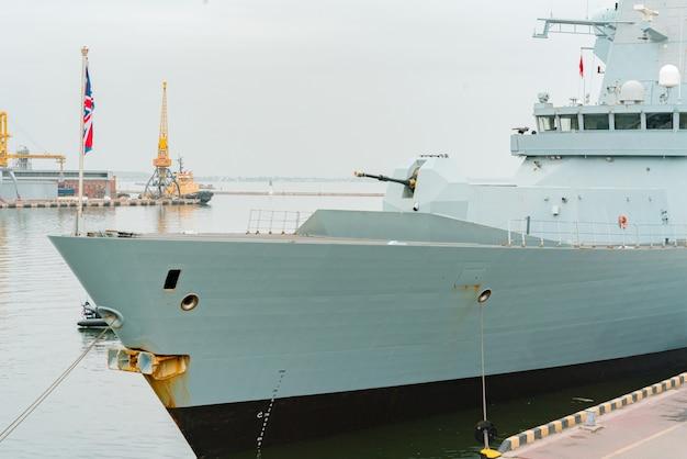 Nez de navire de guerre britannique avec canon amarré à la côte. conflit. arme. bateau. navire. drapeau