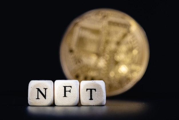 Un nft (jeton non fongible) est un jeton crypto spécial qui utilise la technologie blockchain pour se lier à un actif numérique unique. le mot nft est composé de cubes avec des lettres sur fond cryptocoin doré