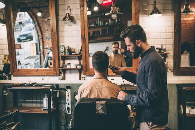 Nice pictur est un salon de coiffure. deux gars sont là. l'un d'eux coupe les cheveux avec un rasoir électrique tandis que l'autre est assis sur une chaise.