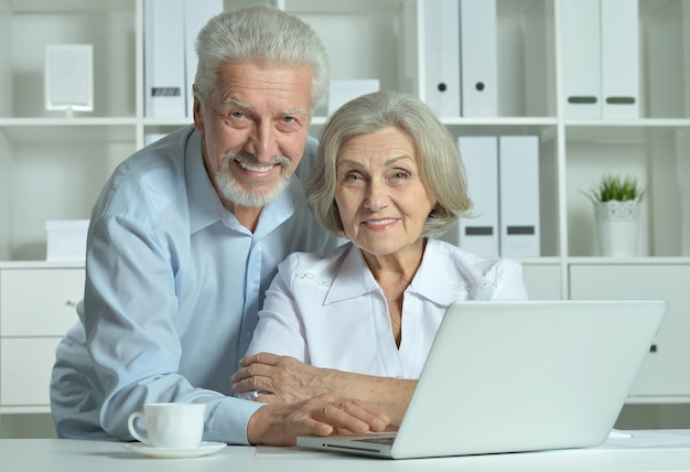 Nice senior doctors with laptop in office
