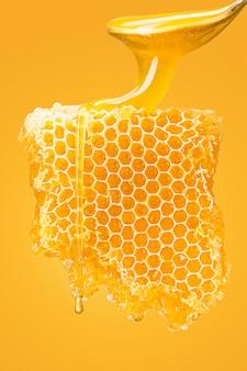 Nid d'abeille doux avec du miel sur fond jaune studio