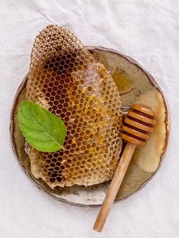 Nid d'abeilles en plaque de céramique et louche sur fond de tissu.