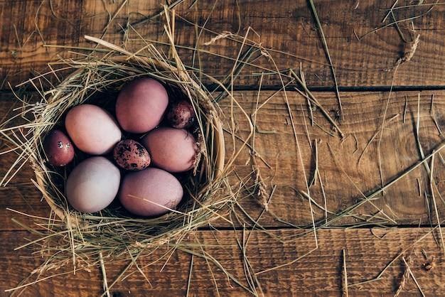 Nid d'ester. vue de dessus des oeufs de pâques colorés dans un bol avec du foin allongé sur une table rustique en bois