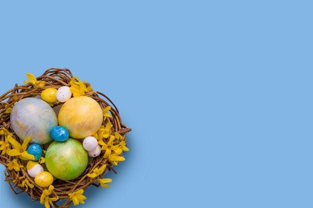 Nid avec des oeufs colorés avec des fleurs sur bleu
