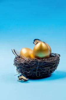 Nid avec des oeufs décoratifs en or et des plumes dans le nid sur fond bleu.