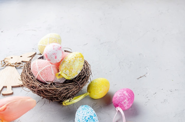 Nid avec oeufs multicolores décoratifs, décorations de pâques, jouets et bouquet de tulipes