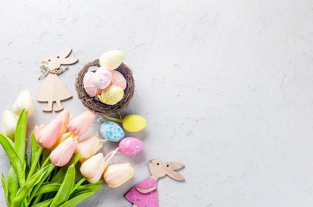 Nid avec oeufs multicolores décoratifs, décorations de pâques et tulipes sur fond de béton gris