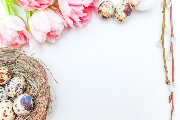 Nid d'oeufs de pâques branche de saule de coton et rose bouquet de fleurs de tulipes fraîches sur fond de bois blanc rustique