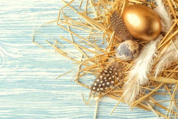 Nid avec des oeufs de pâques sur une surface en bois bleue, vue de dessus avec espace copie