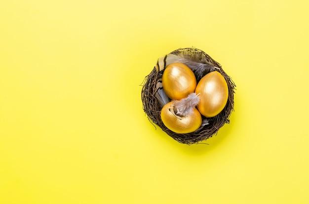 Nid avec oeufs et plumes décoratives or dans le nid sur fond d'or
