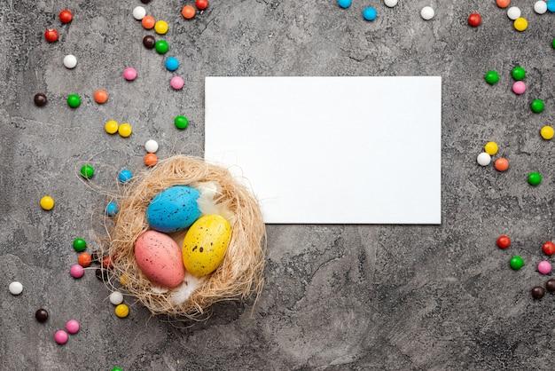 Nid d'oiseau avec des œufs colorés, une carte de pâques vierge et des bonbons