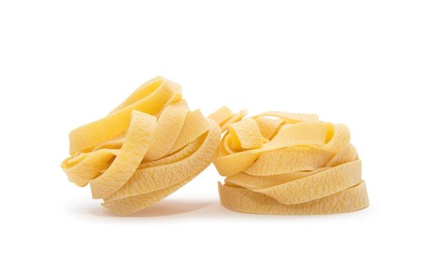 Nid de pâtes. nid non cuit de pâtes tagliatelles isolé sur fond blanc