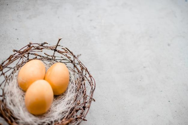 Un nid et plusieurs oeufs avec des bâtons de saule. abstrait gris pierre, notion de joyeuses pâques
