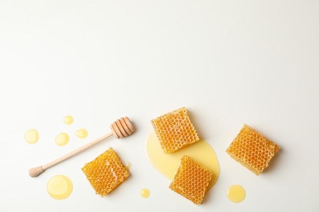 Nids d'abeille et louche sur fond blanc