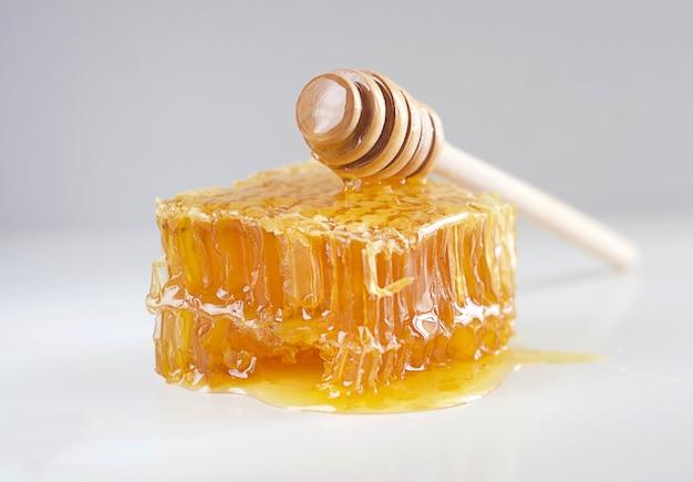 Des nids d'abeilles se trouvent sur la table, sur le dessus se trouve un bâton de miel. esthétique