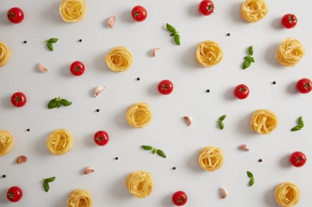 Nids de pâtes crues à base de farine de blé dur, de tomates mûres, d'ail, de feuilles de basilic et de grains de poivre pour la préparation de pâtes. cuisine italienne, concept de cuisine. manger nourrissant. nouilles sur fond blanc