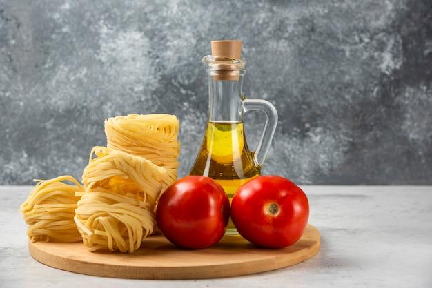 Nids de pâtes crues, bouteille d'huile d'olive et tomates sur plaque en bois.