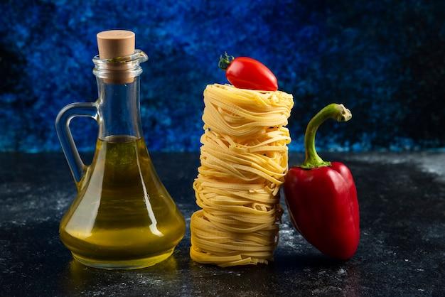Nids de pâtes, huile et légumes sur table en marbre.