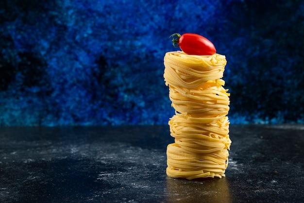 Nids de pâtes non cuites et tomate sur table en marbre.