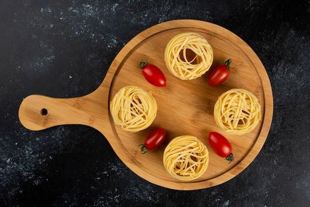 Nids de pâtes non cuites et tomates sur planche de bois.